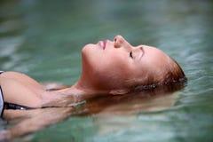 Donna che si distende in acqua Fotografie Stock Libere da Diritti