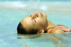 Donna che si distende in acqua Fotografia Stock Libera da Diritti