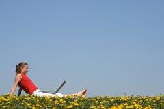 Donna che si distende con il computer portatile Immagini Stock