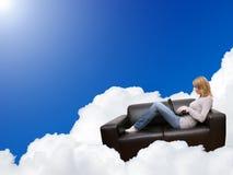 Donna che si distende con il computer portatile in strato sulla nube Fotografie Stock