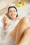 Donna che si distende con il vetro di vino nel bagno Immagini Stock