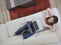 Donna che si distende e che lavora al computer portatile nel paese Immagini Stock