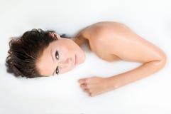 Donna che si distende nel bagno del latte Fotografie Stock Libere da Diritti