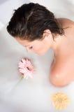 Donna che si distende nel bagno del latte con i fiori Immagini Stock