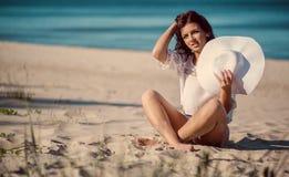 Donna che si distende sulla spiaggia vicino al mare Immagini Stock Libere da Diritti