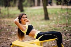 Donna che si esercita con l'attrezzatura di esercizio nel parco pubblico Donna in un addestramento con simulatore di sport sul ca Fotografia Stock