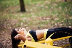 Donna che si esercita con l'attrezzatura di esercizio nel parco pubblico Donna in un addestramento con simulatore di sport sul ca Fotografie Stock
