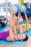 Donna che si esercita con la palla medica nel club di forma fisica Immagine Stock Libera da Diritti