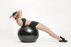 Donna che si esercita con la sfera di forma fisica Immagini Stock Libere da Diritti