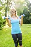 Donna che si esercita con le teste di legno Immagine Stock