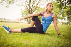 Donna che si esercita mentre sedendosi sull'erba Fotografia Stock