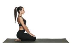 Donna che si esercita sulla stuoia di yoga Isolato su bianco Immagini Stock