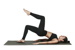 Donna che si esercita sulla stuoia di yoga Isolato su bianco Fotografia Stock Libera da Diritti
