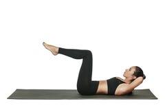 Donna che si esercita sulla stuoia di yoga Isolato su bianco Fotografia Stock