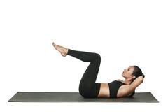 Donna che si esercita sulla stuoia di yoga Isolato su bianco Immagine Stock