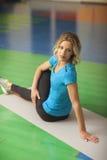 donna che si esercita sulla stuoia nella classe di forma fisica Donna adatta che allunga la sua gamba per riscaldare Immagine Stock Libera da Diritti