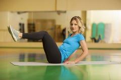 donna che si esercita sulla stuoia nella classe di forma fisica Allenamento femminile Immagini Stock
