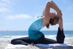 Donna che si esercita in Yogo alla spiaggia Immagini Stock Libere da Diritti