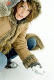 Donna che si inginocchia nella neve Immagini Stock