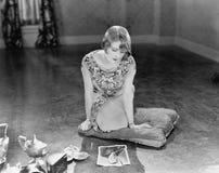 Donna che si inginocchia su un cuscino che esamina un'immagine lacerata di un uomo (tutte le persone rappresentate non sono viven Fotografia Stock