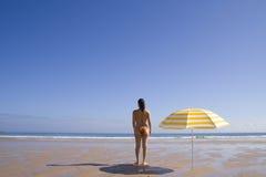 Donna che si leva in piedi alla spiaggia immagini stock libere da diritti