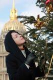 Donna che si leva in piedi l'albero di Natale vicino Fotografia Stock