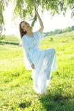 Donna che si leva in piedi sotto l'albero Immagini Stock
