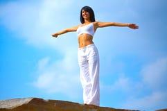 Donna che si leva in piedi su una roccia Fotografia Stock