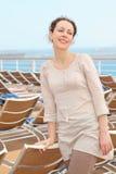Donna che si leva in piedi sulla piattaforma della nave da crociera Immagine Stock