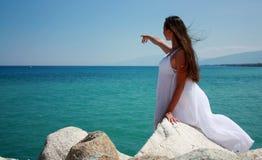Donna che si leva in piedi sulle pietre in vestito bianco Immagini Stock