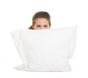 Donna che si nasconde dietro il cuscino isolato su bianco Fotografia Stock Libera da Diritti