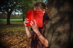 Donna che si nasconde dietro il libro nel parco Immagine Stock