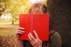 Donna che si nasconde dietro il libro nel parco Fotografia Stock