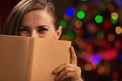 Donna che si nasconde dietro il libro vicino agli indicatori luminosi di natale Immagini Stock