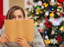 Donna che si nasconde dietro il libro vicino all'albero di Natale Immagine Stock