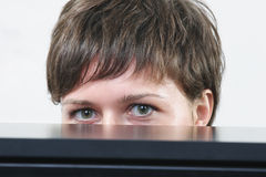 Donna che si nasconde dietro lo scrittorio Immagini Stock