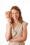 Donna che si nasconde nell'ambito della maschera felice. Fotografia Stock