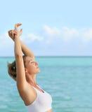 Donna che si rilassa accanto al mare ed all'allungamento Fotografia Stock