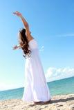 Donna che si rilassa alla spiaggia con le armi aperte godendo della sua libertà Immagine Stock Libera da Diritti