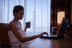 Donna che si rilassa a casa dopo il bagno con il computer portatile Immagine Stock