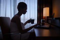 Donna che si rilassa a casa dopo il bagno con il computer portatile Fotografia Stock Libera da Diritti