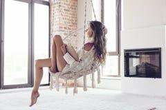 Donna che si rilassa a casa nella sedia d'attaccatura Immagini Stock