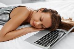 Donna che si rilassa con il computer portatile sul letto Riposo delle free lance tecnologia Immagine Stock