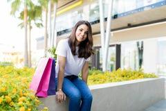Donna che si rilassa dai sacchi di carta dopo la compera fuori del centro commerciale fotografie stock