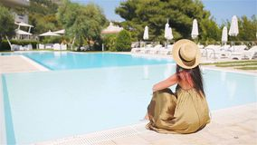 Donna che si rilassa dallo stagno in una località di soggiorno dell'albergo di lusso che gode della vacanza perfetta di festa del video d archivio