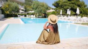 Donna che si rilassa dallo stagno in una località di soggiorno dell'albergo di lusso che gode della vacanza perfetta di festa del archivi video