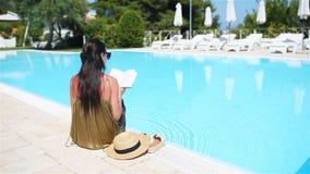 Donna che si rilassa dallo stagno in una località di soggiorno dell'albergo di lusso che gode della vacanza perfetta di festa del stock footage
