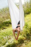 Donna che si rilassa e che pratica yoga antigravità all'albero Immagini Stock