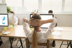 Donna che si rilassa nel luogo di lavoro che si tiene per mano dietro la testa, vista posteriore Immagine Stock