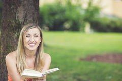 Donna che si rilassa nel parco che legge un libro Immagine Stock